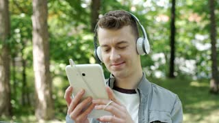 Young man watching something funny on tablet in the park, steadycam shot