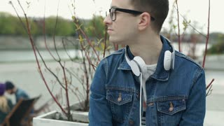 Young man wearing glasses and looks contemplative while relaxing, steadycam shot