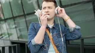 Young man wearing headphones and talking on loudspeaker with someone, steadycam