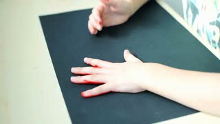 Youngster starts marking his hands on black paper, steadycam shot