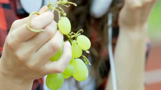 View of bunch of grapes being eaten by a girl, steadycam shot
