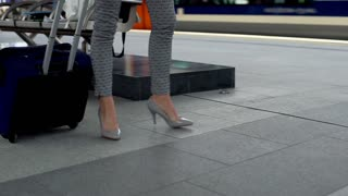 View of businesswoman's legs walking with on the train station