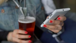 View of female hands holding beer and browsing internet on smartphone