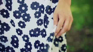 View of female hands touching her dress and feels the material