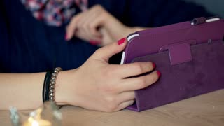 View of female hands using tablet at the table in the cafe