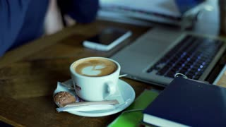 View of the coffee on the table and businessman talking on cellphone, steadycam