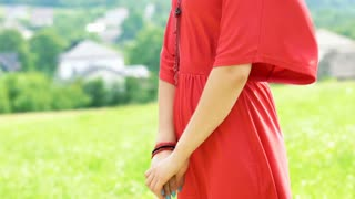 View of woman in red dress standing at sunny day on the meadow