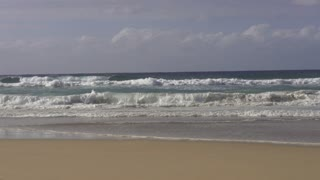 Waves crash over the beach, slow motion shot at 240fps