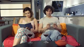 Woma finish reading book and yawning while her boyfriend using smartphone