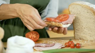 Woman adding basil to the freshly made, tasty sandwich, dolly shot