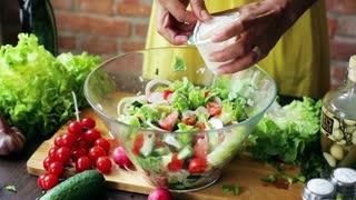 Woman adding cream to the vegetable salad, closeup