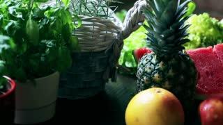 Woman adding fruits to the glass bowl, closeup