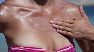 Woman applying sun lotion on her neck, slow motion shot at 120fps