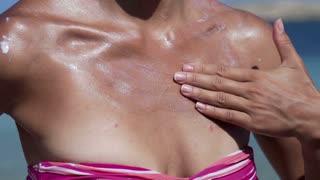 Woman applying sun lotion on her neck, slow motion shot at 240fps