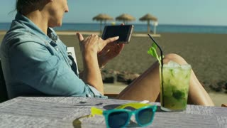 Woman browsing internet on smartphone while sitting on the beach, steadycam shot
