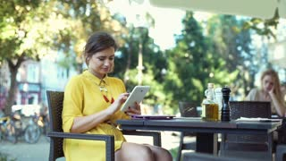Woman browsing internet on tablet and smiling to the camera in the outdoor cafe