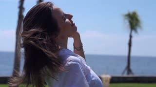 Woman brushing her hair next to the seaside, slow motion shot at 240fps