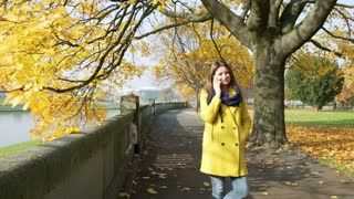 Woman chatting on cellphone and smiling to the camera in the autumnal park