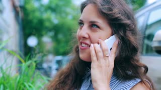 Woman chatting on cellphone and smiling to the camera in the street cafe