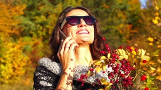 Woman chatting on cellphone in the autumnal scenery, steadycam shot, slow motion