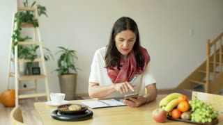 Woman checking something on smartphone and writing in notebook