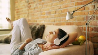 Woman chilling on the sofa and listening music