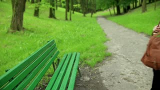 Woman coming to the park and start reading book on the bench