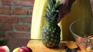 Woman cutting pineapple in the kitchen, closeup
