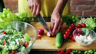 Woman cutting radish on the chopping board, closeup