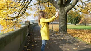 Woman doing selfie on tablet and smiling to the camera in the autumnal park