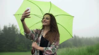 Woman doinge selfie on smartphone and holding an umbrella