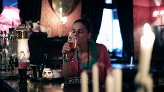 Woman drinking beer in a pub and smiling, steadycam shot