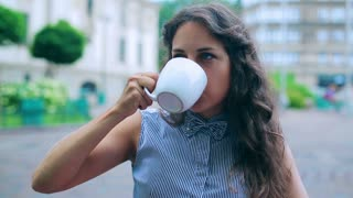 Woman drinking beverage in the street cafe and relax