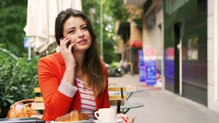 Woman drinking coffee and gossip on cellphone in the street cafe