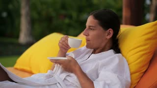 Woman drinking coffee and resting in bed