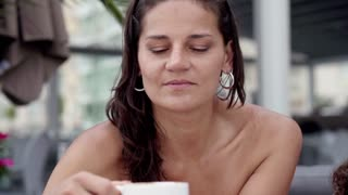 Woman drinking coffee and smiling to the camera, slow motion shot at 120fps