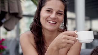 Woman drinking coffee and smiling to the camera, slow motion shot at 240fps