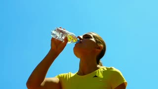 Woman drinking water during her break, steadycam shot, slow motion shot