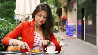 Woman eating breakfast in the street cafe and drinking coffee