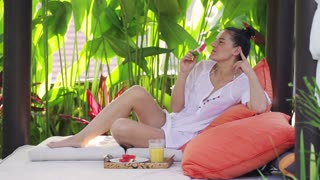 Woman eating watermelon and relaxing in exotic garden