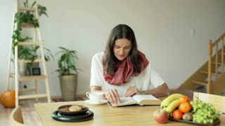 Woman finish reading book and sretching at the table