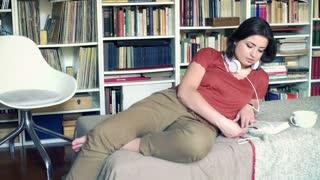 Woman finish reading book and start listening music, steadycam shot