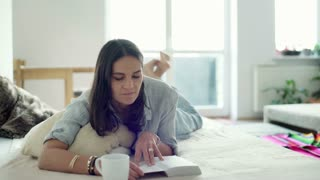 Woman finish reading book and taking a nap on the bed