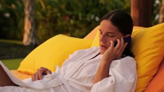 Woman getting bad news on cellphone in the garden