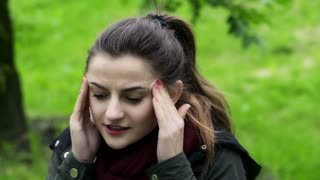 Woman having headache and looking to the camera in the park