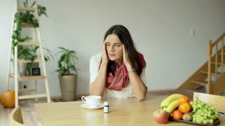 Woman having headache and thinking about taking a pill