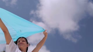 Woman holding sarong on the wind, steadycam shot