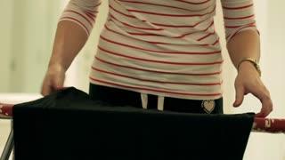 Woman ironing black blouse at home using iron