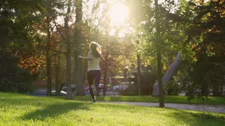 Woman jogging in park at sunny day, slow motion shot at 240fps, steadycam shot