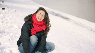 Woman laughing and throwing snowballs to the camera